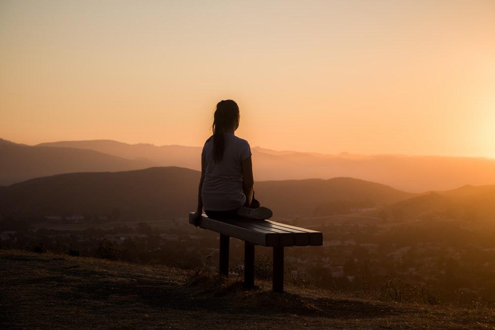 Girl meditating on the hills.