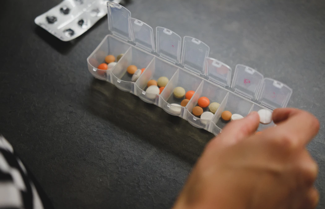 Overmedicated person taking a pill from their medicine box