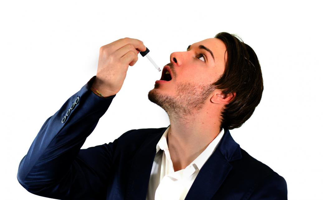 a man taking his daily dose of CBD oil with a dropper bottle