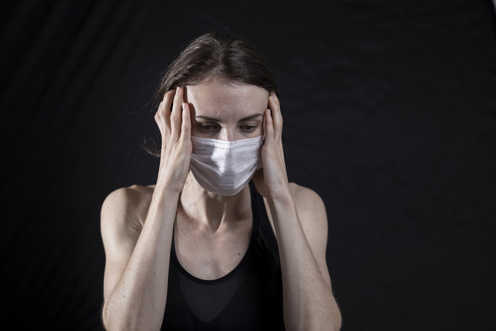 A woman wearing a coronavirus mask experiencing anxiety