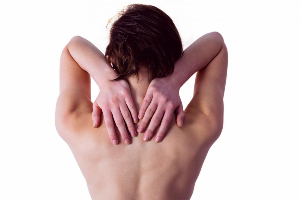 A woman massaging CBD oil on her back muscles