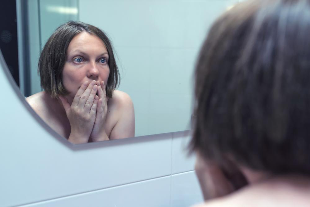A woman checking her face in the mirror for signs of aging