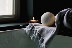 A bath bomb with a candle over a bathtub