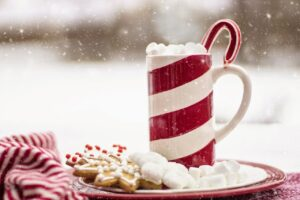 Hot chocolate in a mug with candy canes and some delicious cookies and snowfall