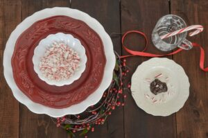 Half-eaten chocolate peppermint cookie with crushed candy canes in a bowl