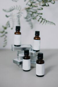 Four bottles of CBD oil are displayed on a white background with a blurred plant behind